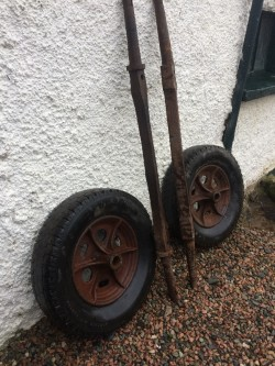Vintage cast iron cart wheels and axles.