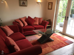 Two red three seater sofas for sale